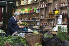 Un homme non identifié achète des fruits et légumes à une stalle sur le marché de ville à Londres le 22 mars, 201 Image stock