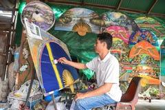 Un homme non identifié font le parapluie de papier Images stock