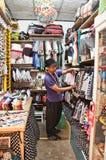 Un homme non identifié tiennent un magasin d'habillement sur le marché de Chatuchak. Image libre de droits