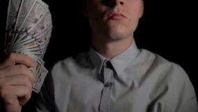 Un homme ondulant une fan des dollars dans l'obscurité mouvement 4k lent banque de vidéos