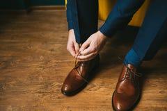 Un homme ou un marié dans un costume bleu attache des dentelles sur les brogues brunes de chaussures en cuir sur un fond en bois  Images stock