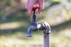 Un homme ouvrant un robinet avec de l'eau service Image libre de droits