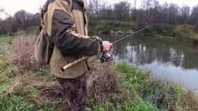 Un homme pêche des poissons sur la rivière en automne banque de vidéos