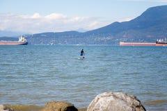 Un homme paddleboarding près de la plage de Locarno, Vancouver, Canada photo stock