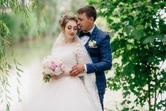 Un homme par derrière les étreintes le sien aimé La fille couvre ses yeux, elle se sent heureuse et calme le jour du mariage Jeun Image libre de droits