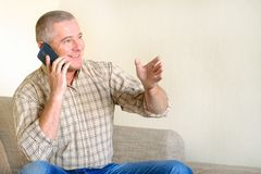 Un homme parlant au téléphone, l'émotion d'une bonne humeur sur son visage photo stock