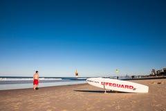 Un homme passant par le côté de la planche de surf d'un maître nageur Photos stock