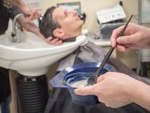 Un homme peint ses cheveux dans un salon de coiffure Technologies innovatrices de restauration de cheveux pour les hommes image libre de droits
