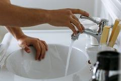 Un homme pendant le matin lave dans une salle de bains lumineuse photographie stock