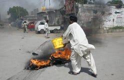 Un homme pleut à torrents l'eau au-dessus de l'incendie Image libre de droits