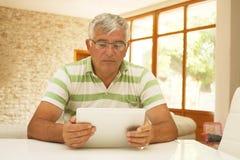 Un homme plus âgé à l'aide d'un comprimé électronique Photographie stock