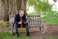 Un homme plus âgé apprécie le livre Image libre de droits