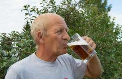Un homme plus âgé avec le plaisir et plaisir boit de la bière froide d'une tasse sur un fond des arbres dans votre jardin Image stock