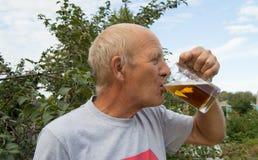 Un homme plus âgé avec le plaisir et plaisir boit de la bière froide d'une tasse sur un fond des arbres dans votre jardin Image libre de droits