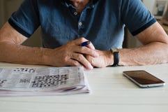 Un homme plus âgé avec les mots croisé et le téléphone Photo libre de droits
