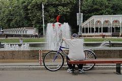 Un homme plus âgé avec une bicyclette se reposant sur un banc et regardant la fontaine en parc de Sokolniki Photographie stock libre de droits