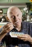Un homme plus âgé avec une caisse de pillule Photos libres de droits