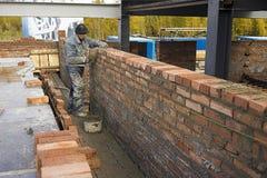 Un homme plus âgé d'aspect caucasien met un mur de briques Photographie stock libre de droits