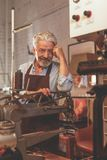 Un homme plus âgé dans un atelier images stock