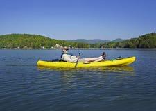 Un homme plus âgé dans le kayak sur le lac mountain Photos stock