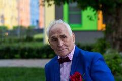 Un homme plus âgé dans une veste bleue dehors Image stock