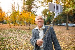 Un homme plus âgé en parc et prises d'automne un monopod avec un téléphone portable Dehors sur la rue Photo stock