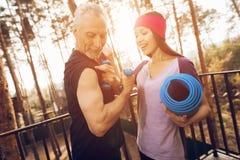 Un homme plus âgé et un instructeur de forme physique parlent dans une maison de repos Photographie stock