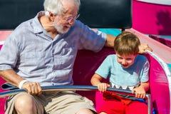 Un homme plus âgé et son jeune tour de petit-fils sur un Carniva de rotation photographie stock