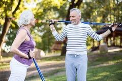 Un homme plus âgé et une femme parlant tout en pratiquant en parc Photo libre de droits