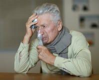 Un homme plus âgé faisant l'inhalation Photographie stock