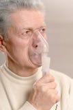 Un homme plus âgé faisant l'inhalation Photos stock