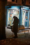 Un homme plus âgé flâne devant un kiosque des livres utilisés pendant Photographie stock