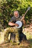 Un homme plus âgé jouant le banjo à l'extérieur Photographie stock libre de droits