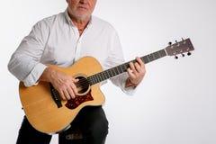 Un homme plus âgé joue une guitare d'isolement sur le fond blanc image stock