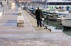 Un homme plus âgé marche le long des bateaux joints dans le port Tarragone L'Espagne 04 01 2016 Image stock