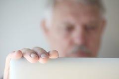 Un homme plus âgé regarde l'ordinateur portable avec l'espace de copie Images stock