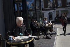 Un homme plus âgé s'assied à une table dans un café de rue lisant un journal images libres de droits