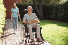 Un homme plus âgé s'assied dans un fauteuil roulant Derrière lui vient une fille Le vieil homme lit un livre Photographie stock libre de droits