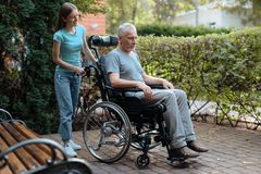 Un homme plus âgé s'assied dans un fauteuil roulant Est tout près sa fille, elle est prête à prendre le vieil homme Photos stock