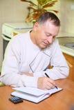 Un homme plus âgé se concentrant sur le travail. Photo libre de droits