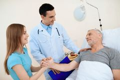 Un homme plus âgé se situe dans une chambre d'hôpital sur un lit Il subit la réadaptation À côté de lui est un docteur image stock