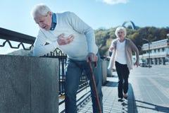 Un homme plus âgé sentant la douleur grave de coeur pendant la promenade Photos libres de droits