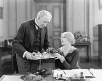Un homme plus âgé servant un thé de femme sur un plateau (toutes les personnes représentées ne sont pas plus long vivantes et auc Photographie stock libre de droits