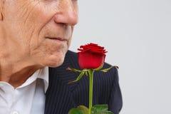 Un homme plus âgé sur un fond blanc, dans un costume futé noir, des supports avec un s'est levé dans sa main Photographie stock