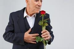 Un homme plus âgé sur un fond blanc, portant un costume élégant noir, sent un parfumé s'est levé dans sa main Image libre de droits