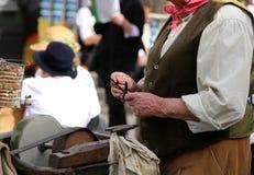 Un homme plus âgé tandis qu'affile le couteau en meule Image libre de droits