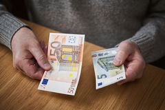 Un homme plus âgé tenant des billets de banque d'une dénomination d'euro de l'euro 50 et 5 Image stock
