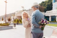 Un homme plus âgé tient un bouquet des fleurs derrière de retour Une femme est venue à une date et aux essais pour remarquer sur  Photos stock