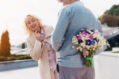 Un homme plus âgé tient un bouquet des fleurs derrière de retour Une femme est venue à une date et aux essais pour remarquer sur  Photographie stock libre de droits