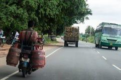 Un homme portant cinq cylindres de gaz dans un vélomoteur Photos libres de droits